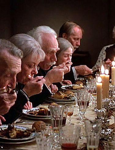 Pessoas à mesa saboreando pratos à luz de vela
